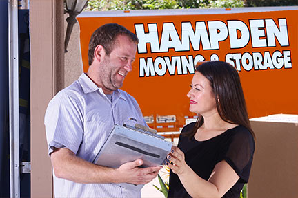 Man and women talking in front of a Hampden moving truck.