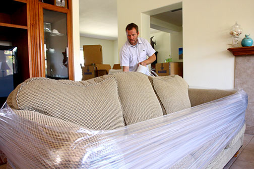 Man with and tan couch in a home getting wrapped for moving..