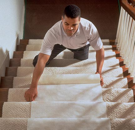 Man on stairs placing carpet.