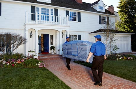 Two men moving a blue covered couch into a white and black home.