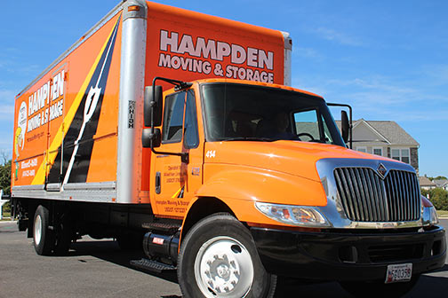 Orange Hampden truck parked with a blue sky background.